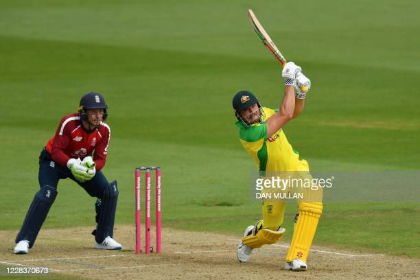 Australia's Marcus Stoinis hits a six as England's Jos Buttler keeps wicket during the international Twenty20 cricket match between England and...