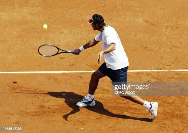 Australia's Mark Phillipoussis hits a backhand return as he practises on the newly laid clay surface on centre court at the Sydney International...