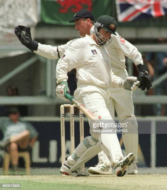 Australia's Mark Taylor flattens the pitch as England wicketkeeper Alec Stewart receives the ball from the field