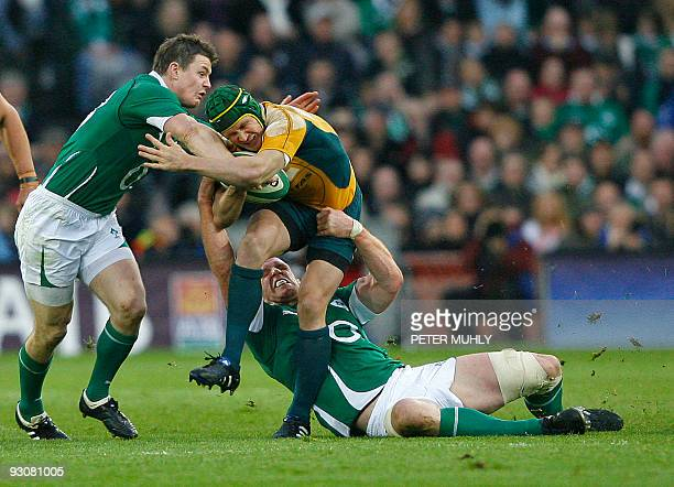 Australia's Matt Giteau breaks a tackle from Ireland's Brian O'Driscoll and Paul O'Connell during an international rugby union match at Croke Park on...