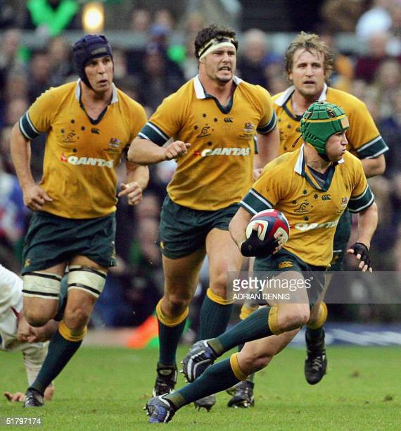Australia's Matt Giteau runs the ball in front of his forwards Daniel Vickerman Al Baxter and Bill Young against England during the Investec...