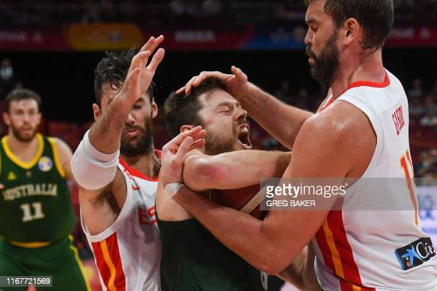TOPSHOT Australia's Matthew Dellavedova fights for the ball with Spain's Rudy Fernandez and Marc Gasol during the Basketball World Cup semifinal game...