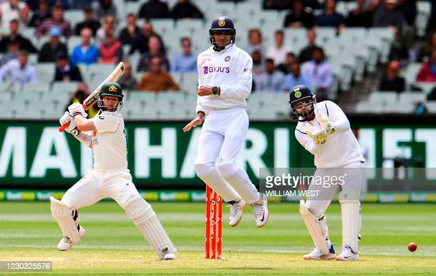 Australia's Matthew Wade plays a shot as India's Shubman Gill jumps in the air to avoid a direct hit on the third day of the second cricket Test...