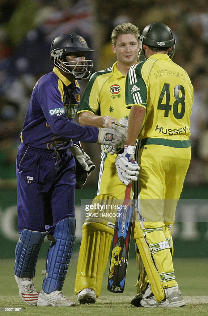 Australia's Michael Hussey (R) is congratulated by Sri Lankan wicket-keeper Kumar Sangakkara (L) as Michael Clarke looks on after Australian won the One Day International played at the Adelaide Oval 26 January 2006. Australia won the match 5-219 beating Sri Lanka's total of 218. Australia now leads the competition on 14 points with Sri Lanka on 9 and South Africa on 8.