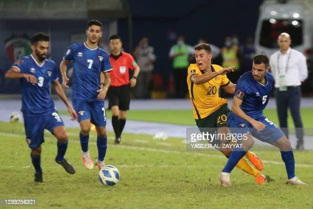 Australia's midfielder Chris Ikonomidis is marked by Kuwait's defender Fahd al-Hajeri during the 2022 FIFA World Cup qualification group B football...