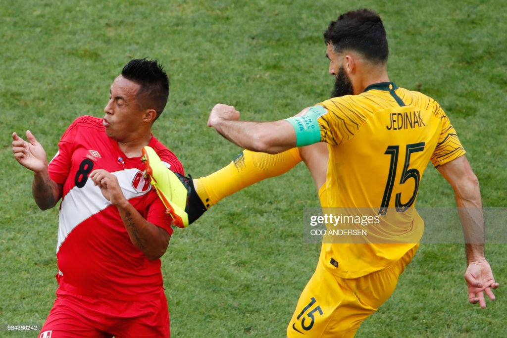 TOPSHOT - Australia's midfielder Mile Jedinak (R) fouls Peru's midfielder Christian Cueva during the Russia 2018 World Cup Group C football match between Australia and Peru at the Fisht Stadium in Sochi on June 26, 2018. (Photo by Odd ANDERSEN / AFP) / RESTRICTED