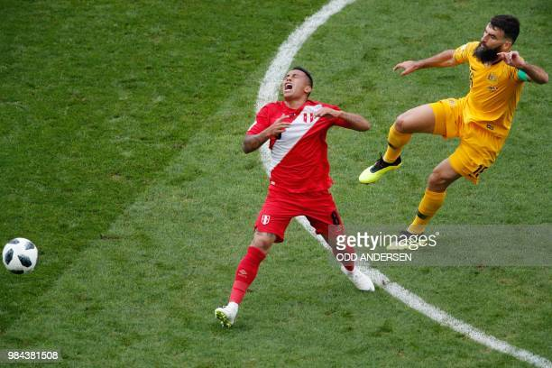 TOPSHOT Australia's midfielder Mile Jedinak fouls Peru's midfielder Christian Cueva during the Russia 2018 World Cup Group C football match between...