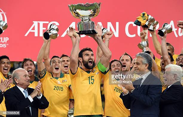 Australia's Mile Jedinak celebrates as he lifts the trophy after beating South Korea in the AFC Asian Cup football final at Stadium Australia in...