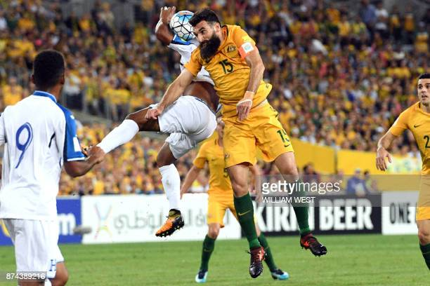 Australia's Mile Jedinak fights for the ball with Honduras' players during their 2018 World Cup qualification playoff football match at Stadium...