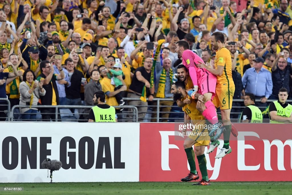 Australia's Mile Jedinak (15) is congratulated by teammates after scoring against Honduras during their 2018 World Cup qualification play-off football match at Stadium Australia in Sydney on November 15, 2017. / AFP PHOTO / William WEST / -- IMAGE