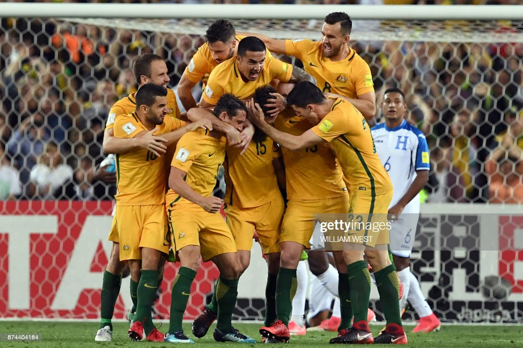 Australia's Mile Jedinak (C) is mobbed by his teammates after scoring against Honduras during their 2018 World Cup qualification play-off football match at Stadium Australia in Sydney on November 15, 2017. / AFP PHOTO / William WEST / -- IMAGE