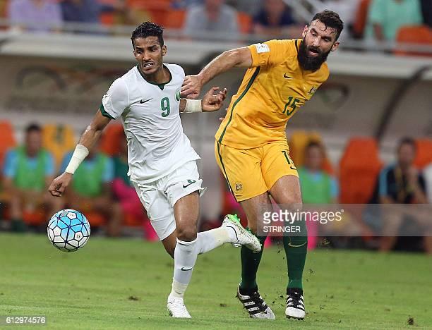 Australia's Mile Jedinak marks Saudi's Nawaf Alabid during the 2018 FIFA World Cup Qualifiers match between Saudi Arabia and Australia at the King...