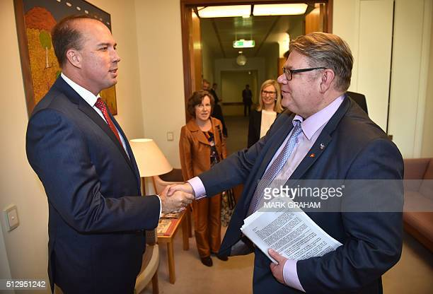 Australia's Minister for Immigration and Border Protection Peter Dutton shakes hands with Finland's Foreign Minister Timo Soini during the latter's...