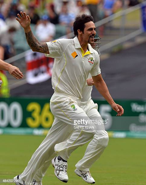 Australia's Mitchell Johnson celebrates his first wicket of the day England's batsman Alastair Cook on the day four of the second Ashes cricket Test...