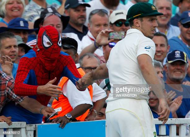 Australias Mitchell Marsh signs autographs for a person in fancy dress during play on the third day of the fifth Ashes cricket test match between...