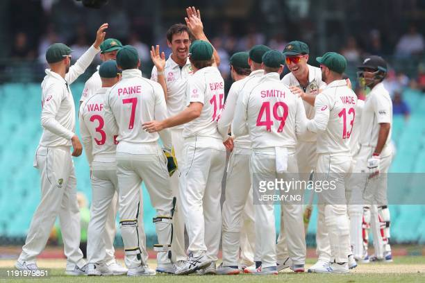 Australia's Mitchell Starc celebrates with teammates after taking the wicket of New Zealand captain Tom Latham during the fourth day of the third...
