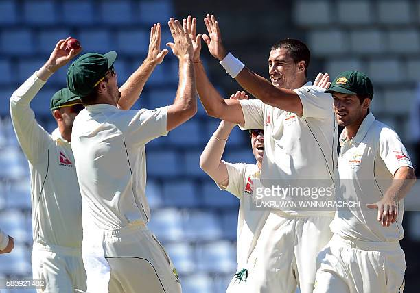 Australia's Mitchell Starc celebrates with teammates the dismissal of Sri Lanka's Dimuth Karunaratne during the third day of the opening Test match...