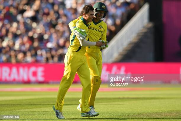 Australia's Mitchell Swepson is congratulated by Australia's Alex Carey after taking the wicket of England's Jos Buttler for 61 during the Twenty20...