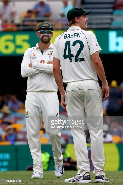 Australia's Nathan Lyon and Cameron Green smile while fielding during the play on day two of the fourth cricket Test match between Australia and...