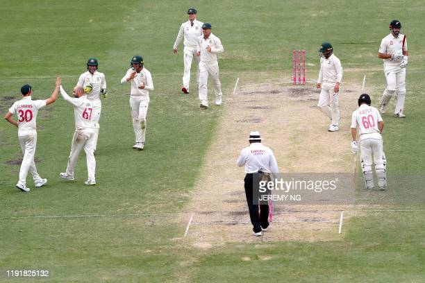 Australias Nathan Lyon celebrates with his teammates after dismissing New Zealands Will Somerville during the third day of the third cricket Test...