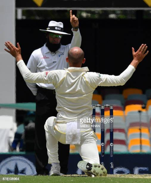 Australia's Nathan Lyon gestures toward umpire Aleem Dar for a successful leg-before-wicket appeal against England's batsman England's Moeen Ali on...