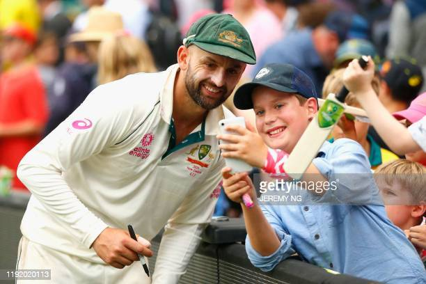 Australia's Nathan Lyon poses for a selfie with a fan during the fourth day of the third cricket Test match between Australia and New Zealand at the...