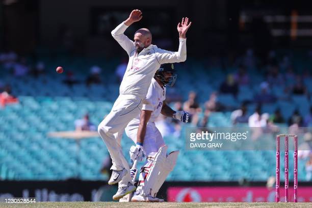 Australia's Nathan Lyon reacts next to India's Hanuma Vihari as a fielder throws the ball to the stumps during the fifth day of the third cricket...