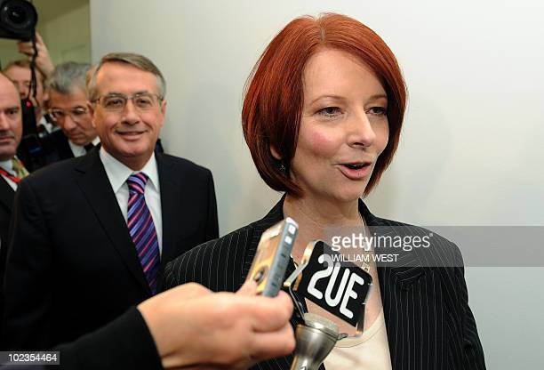 Australia's new prime minister Julia Gillard smiles as she and new deputy prime minister Wayne Swann leave a meeting after Gillard became Australia's...