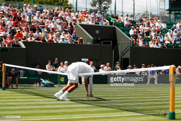 Australia's Nick Kyrgios bends over the net during his men's singles first round match against Australia's Jordan Thompson on the second day of the...