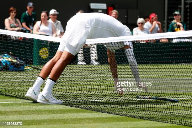 TOPSHOT Australia's Nick Kyrgios bends over the net during his men's singles first round match against Australia's Jordan Thompson on the second day...