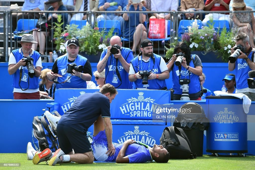 TOPSHOT - Australia's Nick Kyrgios receives medical treatment after slipping against Donald Young of the US in their men's singles 1st round match at the ATP Aegon Championships tennis tournament at Queen's Club in west London on June 19, 2017. Nick Kyrgios suffered a fresh injury blow ahead of Wimbledon as the Australian star was forced to retire from his Queen's Club first round clash with Donald Young on Monday. /