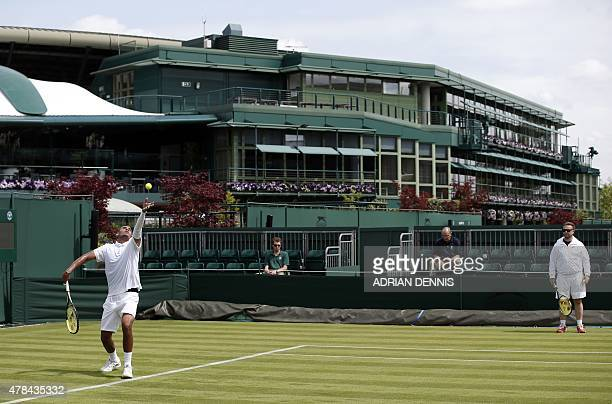 Australia's Nick Kyrgios serves during a practice session hitting against Switzerland's Roger Federer ahead of the 2015 Wimbledon Championships at...