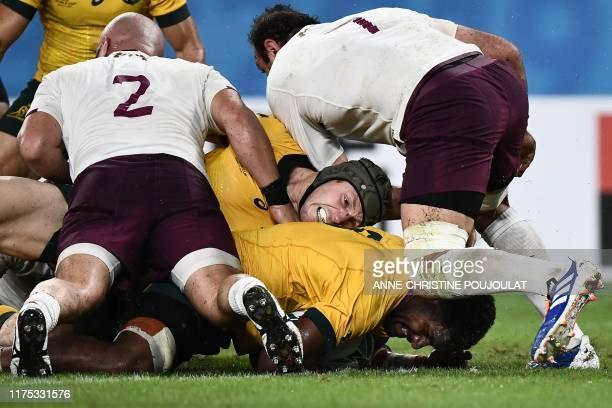 Australia's number 8 Isi Naisarani and Australia's flanker David Pocock are tackled by Georgia's hooker Shalva Mamukashvili and Georgia's flanker...