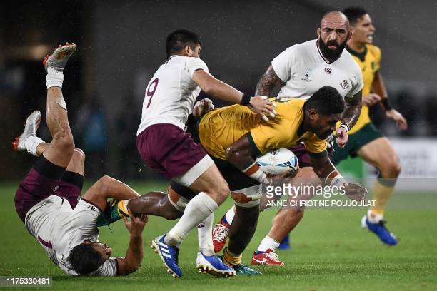 Australia's number 8 Isi Naisarani is tackled by to evade Georgia's centre Davit Kacharava and Georgia's scrum-half Gela Aprasidze during the Japan...