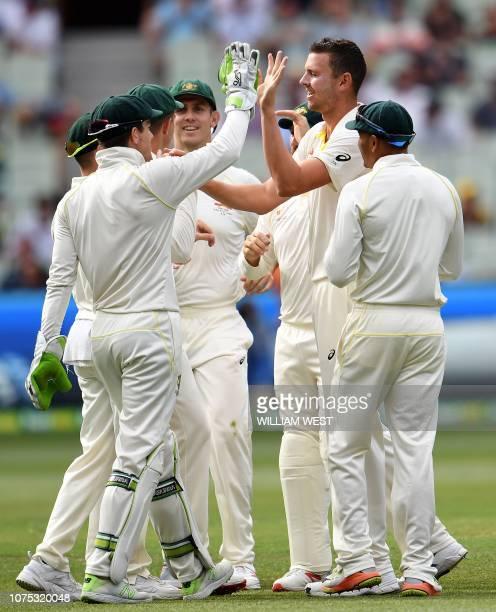 Australia's paceman Josh Hazlewood celebrates taking the wicket of India's batsman Rohit Sharma with teammates during day three of the third cricket...