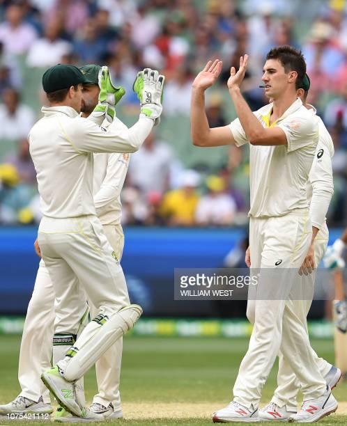 Australia's paceman Pat Cummins celebrates his wicket of India's batsman Ravindra Jadeja with team's captain Tim Paine during day four of the third...