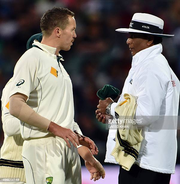 Australia's paceman Peter Siddle talks with umpire Sundaram Ravi following a rejection of his legbeforewicket appeal against New Zealand's Brendon...