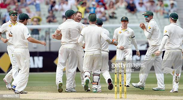 Australia's paceman Ryan Harris is congratulated by teammates after dismissing India's batman Ravi Ashwin on the third day of the third cricket Test...
