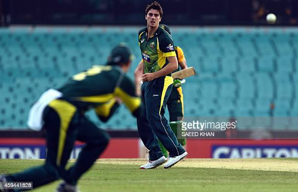Australia's pacer Pat Cummins looks back as his teammate George Bailey takes a successfull catch out of South Africa's batsman Faf du Plessis during...