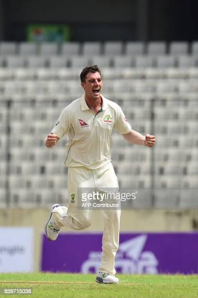 Australia's Pat Cummins celebrates the dismissal of the Bangladesh's Soumya Sarkar during the first day of the first Test cricket match between...