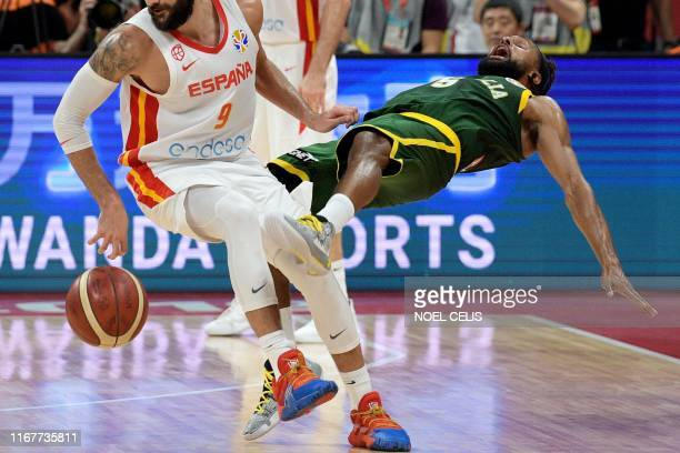 TOPSHOT Australia's Patty Mills falls on the court as he fights for the ball with Spain's Ricky Rubio during the Basketball World Cup semifinal game...