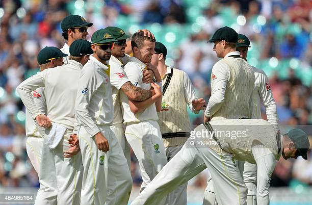 Australias Peter Siddle is congratulated by teammates after taking the wicket of England's Stuart Broad during play on the fourth day of the fifth...
