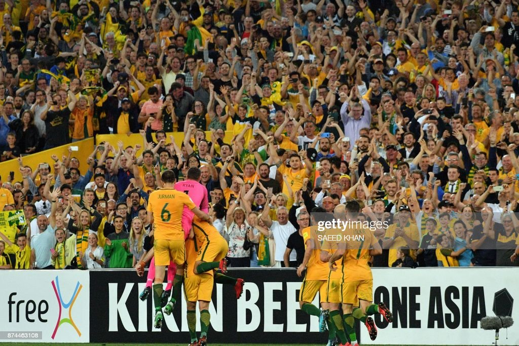 Australia's players celebrate after Mile Jedinak (obscured) scored against Honduras in their 2018 World Cup qualification play-off football match at Stadium Australia in Sydney on November 15, 2017. / AFP PHOTO / Saeed KHAN / -- IMAGE