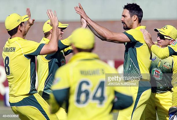 Australia's players celebrate after taking a wicket during a oneday international triangular series cricket match between Australia and South Africa...