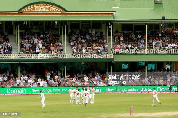 Australia's players celebrate taking a wicket during the fourth day of the third cricket Test match between Australia and New Zealand at the Sydney...