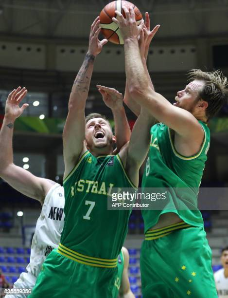 Australia's players Mitch Creek and Brad Newley jump for the ball as they fight against New Zealand's player during their 2017 FIBA Asia Cup...