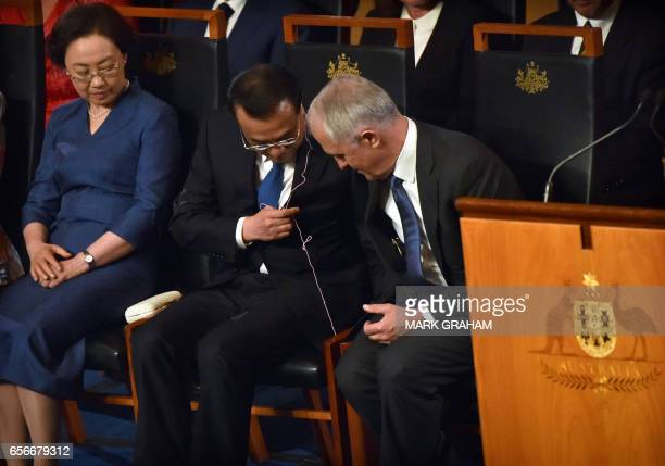 Australia's Prime Minister Malcolm Turnbull helps China's Premier Li Keqiang with his translation earpiece as his wife Cheng Hong looks on during a...