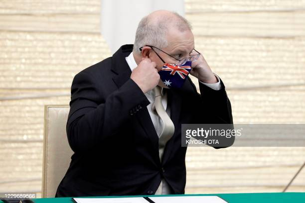 Australia's Prime Minister Scott Morrison removes his face mask as he arrives to attend a signing ceremony with Japan's Prime Minister Yoshihide Suga...