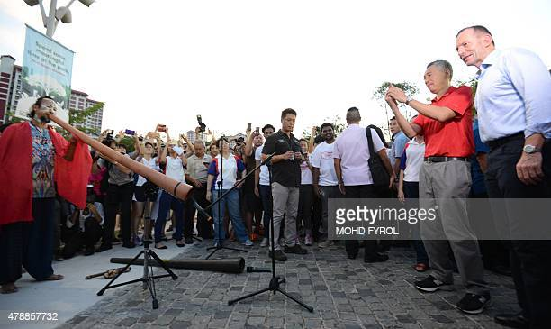 Australia's Prime Minister Tony Abbott and Singapore Prime Minister Lee Hsien Loong was a performer play the didgeridoo during a visit to Bishan Park...