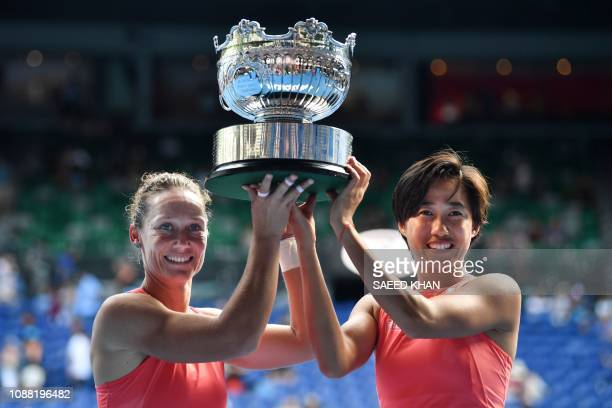 Australia's Samantha Stosur and China's Zhang Shuai celebrate with the championship trophy after winning the women's doubles final against Hungary's...